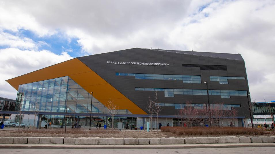 The Barrett CTI building from across the parking lot. The building is grey with orange and glass accents